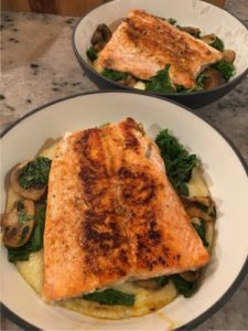 salmon with veggies over cheesy grits